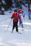 运动员在积雪的风景的孩子滑雪横越全国的连续冬天竞争中 免版税图库摄影