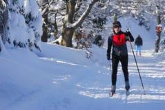 运动员在积雪的风景的孩子滑雪横越全国的连续冬天竞争中 免版税库存图片