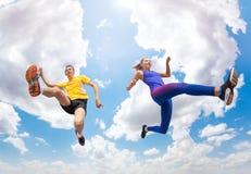 运动员在空气保持,当跳反对天空时 免版税图库摄影