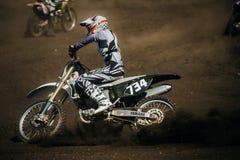 运动员在轨道的摩托车骑士骑马在土下轮子  库存照片
