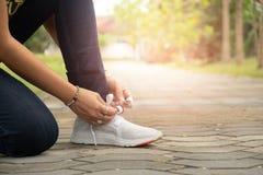 运动员坐下对鞋子的绳索 免版税图库摄影