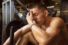 年轻运动员坐健身房设备用在forehea的手 库存图片