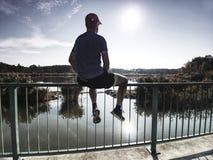 运动员坐扶手栏杆在公园 跑步的人的脚 库存照片