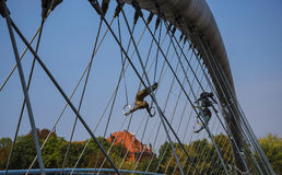 运动员壮观的平衡的古铜色雕象Bernatka人行桥的在河维斯瓦河在克拉科夫波兰 免版税库存图片