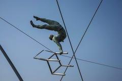 运动员壮观的平衡的古铜色雕象Bernatka人行桥的在河维斯瓦河在克拉科夫波兰 免版税图库摄影