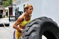 运动员女性解决与一个巨大的轮胎,转动和flippin 免版税库存照片
