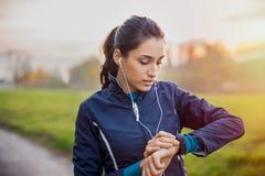 运动员妇女检查smartwatch 免版税库存图片