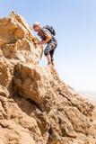 运动员常设沙漠山岩石峭壁土坎边缘landsca 免版税图库摄影