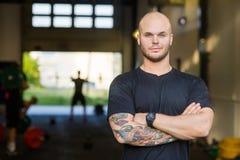 运动员常设胳膊横渡在健身房 免版税图库摄影