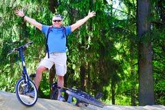 运动员幸运投掷了他的手对边 在山的立场在自行车附近 愉快地宽微笑 免版税图库摄影