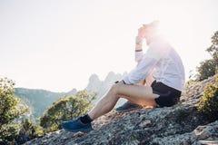 运动员或人休息画象在山顶部的 免版税库存照片