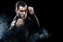 运动员战斗在拳击笼子的泰拳拳击手 隔绝在与烟的黑背景 复制空间 图库摄影