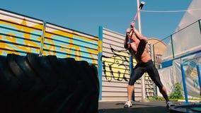 运动员敲打有室外的锤子的橡胶轮胎 股票视频