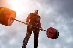 运动员有拿着重的杠铃的困难 免版税库存照片