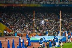 运动员照相机闪光撑竿跳高 免版税库存照片