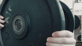 运动员爱好健美者在杠铃上把重量放 股票视频
