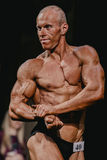 运动员爱好健美者费劲的二头肌,侧视图 免版税图库摄影