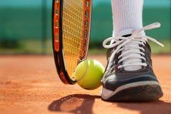 运动员的腿在网球拍和球附近的 免版税库存图片