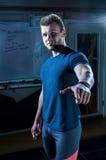 年轻运动员站立在健身房并且在他自己前面指向 库存图片
