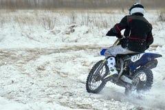 运动员竟赛者人履行在一辆摩托车的快速的乘驾在路极端 赛马跑道是非常参差不齐的 图库摄影