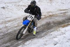 运动员竟赛者人履行在一辆摩托车的快速的乘驾在路极端 赛马跑道是非常参差不齐的 库存照片