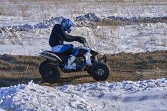运动员竟赛者人履行在ATV的快速的乘驾在路极端 赛马跑道是非常参差不齐的 免版税库存照片