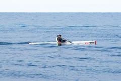 运动员训练在皮船在海的冬天早晨在海岸附近 库存照片