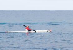运动员训练在皮船在海的冬天早晨在海岸附近 库存图片