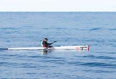 运动员训练在皮船在海的冬天早晨在海岸附近 免版税库存图片