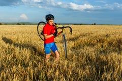 运动员负担领域的自行车 佩带的体育齿轮、盔甲和玻璃 自然本底 美丽,蓝天 库存照片