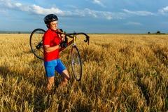 运动员负担领域的自行车 佩带的体育齿轮、盔甲和玻璃 自然本底 美丽,蓝天 免版税库存照片