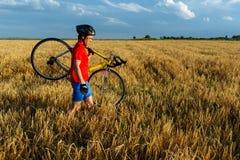 运动员负担领域的自行车 佩带的体育齿轮、盔甲和玻璃 自然本底 美丽,蓝天 图库摄影