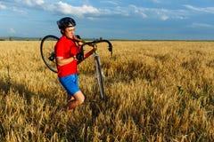 运动员负担领域的自行车 佩带的体育齿轮、盔甲和玻璃 自然本底 美丽,蓝天 免版税库存图片