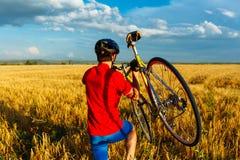 运动员负担领域的自行车 回到视图 佩带的体育齿轮和盔甲 自然本底 美丽,蓝天 免版税图库摄影