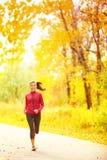 运动员跑在秋天秋天森林里的赛跑者妇女 免版税图库摄影