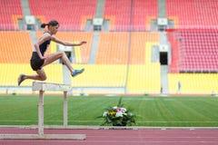 运动员跳克服障碍 免版税库存照片