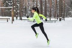 运动员运行在冷的降雪的天气的妇女赛跑者 心脏街道训练马拉松跑步 免版税库存照片