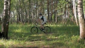 运动员通过森林骑自行车在一个美好的晴天 优秀心情和身体好 股票录像