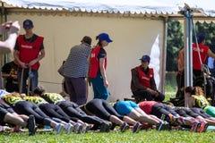 运动员队完成俯卧撑任务在接力赛的 莫斯科健身节日在公园 库存照片