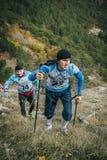 年轻运动员马拉松运动员是在他的山行迹的对手前 库存照片