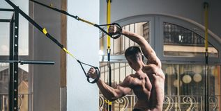 运动员,运动员,肌肉强壮男子行使与trx圈,在背景的窗口 有裸体躯干的人和肌肉 库存图片