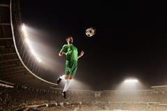 运动员chesting的足球在体育场内在晚上 免版税图库摄影