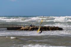 运动和静止、海波浪和三角浪在大风天:行动的风帆冲浪者和年长妇女 库存照片