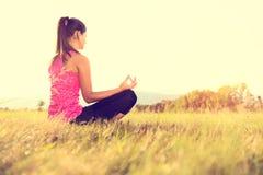 年轻运动在一个草甸的女子实践的瑜伽日落的 免版税图库摄影