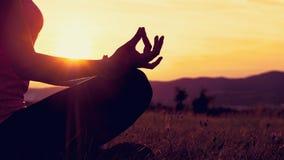 年轻运动在一个草甸的女子实践的瑜伽日落的 图库摄影