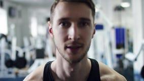 运动在健身房的人举的哑铃 股票录像