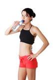 运动在运动服的妇女饮用水 图库摄影