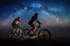 运动夫妇乘坐自行车在晚上在满天星斗的天空下 免版税图库摄影
