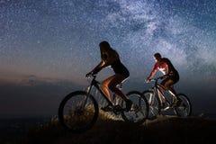 运动夫妇乘坐自行车在晚上在满天星斗的天空下 库存图片