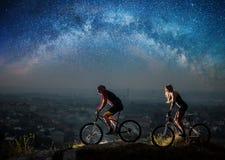 运动夫妇乘坐自行车在晚上在满天星斗的天空下 免版税库存照片